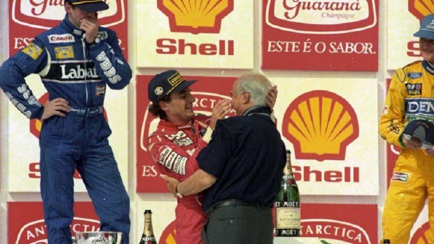 Senna y Fangio se abrazan ante la atenta mirada y admiración de Michael Schumacher