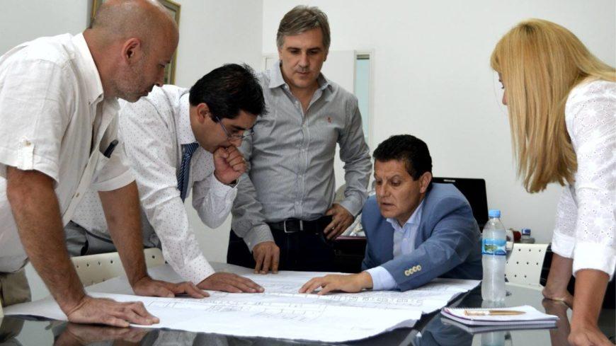 Llaryora observando los planos de la obra
